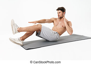 Photo of young shirtless man lying on fitness mat and doing criss cross crunches while working out