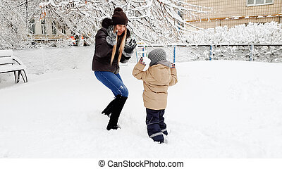 Photo of young smiling blond woman playind in snow balls with her cute son in jacket and hat on the playground in the Park