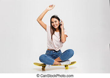 Photo of young smiling brunette woman in white headphones...
