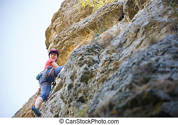 Photo of young sportswoman in protective helmet climbing on mountain