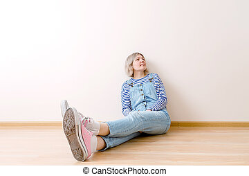 Photo of young woman sitting on floor