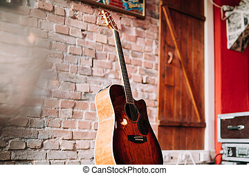 guitar with a brick wall in the backgraund