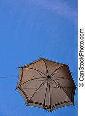 Old umbrella against blue sky