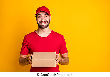 Photo portrait of curious courier holding carton box for delivery looking blank space isolated on vibrant yellow color background