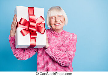 Photo portrait of curious old lady holding present box near ear shaking guessing what's inside isolated on pastel blue colored background.