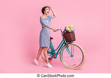 Photo portrait of excited screaming girl watching far with hand at forehead holding bicycle isolated on pastel pink colored background