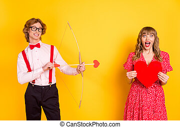 Photo portrait of guy with arrow bow and amazed girl keeping red heart isolated on vibrant yellow background