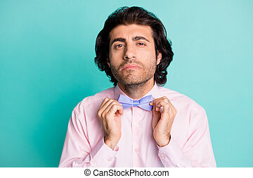 Photo portrait of handsome gentle man dressed pink outfit preparing date fixing bow tie isolated teal color background