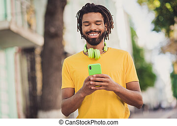Photo portrait of man with dreadlocks wearing headphones smiling using smartphone walking on street