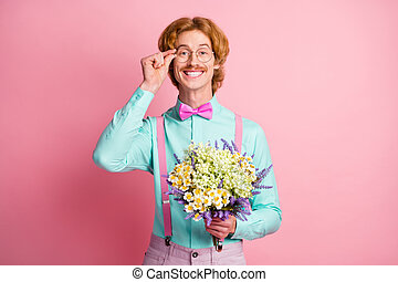 Photo portrait of red haired man smiling touching spectacles giving flowers on date isolated on pastel pink color background