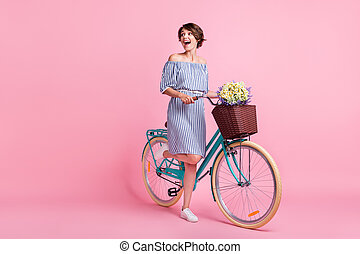 Photo portrait of woman holding bicycle with front basket flowers standing on one leg isolated on pastel pink colored background