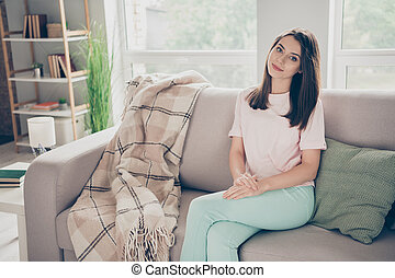 Photo portrait of young woman sitting on sofa with crossed legs indoors