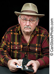 senior male with money issues on black background