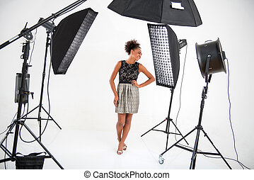 Full-length portrait of lovely African model wearing wonderful evening dress standing in front of projectors looking at someone