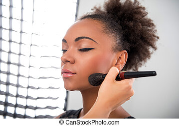 Half-length portrait of lovely African model standing in the studio with closed eyes waiting until her make-up will be ready