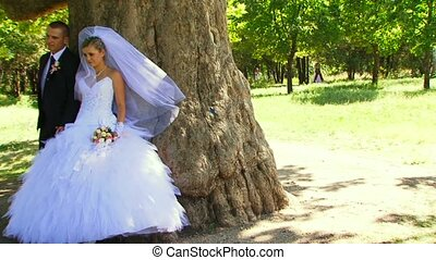 Photo Session Of The Newlyweds Near A Tree.