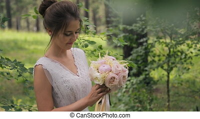 Photo shoot of bride in wedding dress sniffing flowers in forest