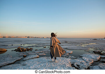 Photo shoot young woman in the Gulf of Finland at winter in St. Petersburg.