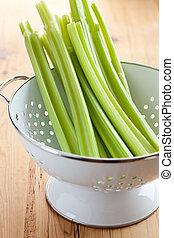 green celery sticks in colander - photo shot of green celery...