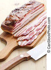 photo shot of slices smoked bacon on kitchen table