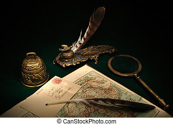 Still life with a table desk set, magnifier, bell and map