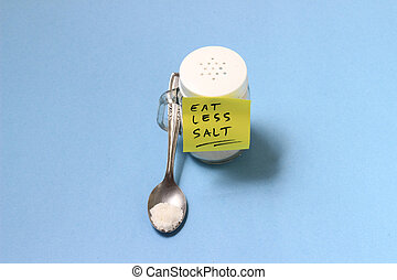spilled salt from small shaker at blue paper background
