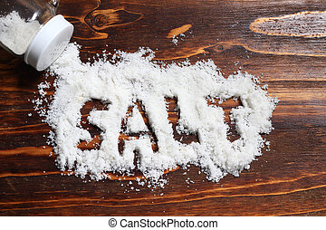 spilled salt from small shaker at wooden board background