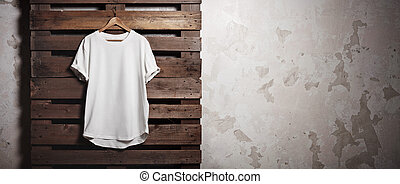Photo white tshirt hanging in front of concrete wall. Wide...