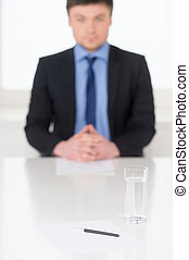 Photo with blur man on background and CV on foreground. Concept of holding successful interview.
