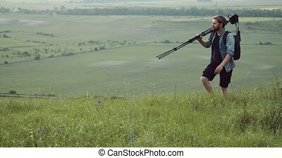 Photograher walking on hill with tripod and digital camera...