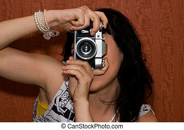 photograph - beauty girl shooting the retro camera on red...