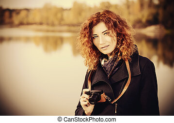 Autumn style. Beautiful smiling woman with bright foxy hair photographs. Beauty, fashion.