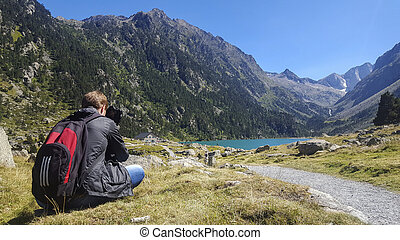 Photograph of a sitting boy taking photographs of the landscape