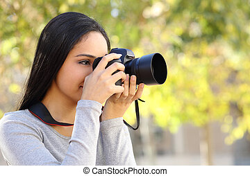Photograph woman learning photography in a park happy with a...