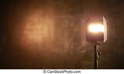 Photographer adjusts lighting equipment on a background of...