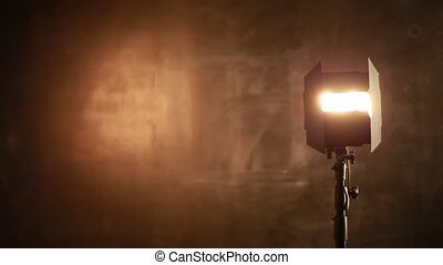 Photographer adjusts lighting equipment on a background of chalkboard. Working in photo studio