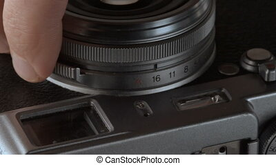 Photographer adjusts the aperture in the camera