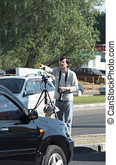 photographer among cars in city points by hand