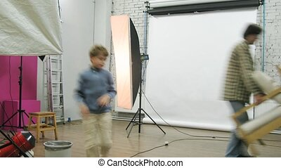 Photographer and his kid adjust equipment at photo studio,...