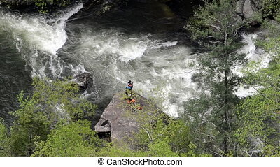 Photographer and Kayaker Passes By - A kayaker runs a rapid...