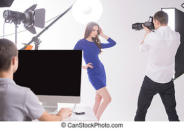Photographer and model at studio. Young man photographing...