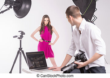 Photographer and model. Photographer holding camera and looking at fashion model