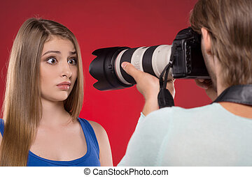 Photographer and model. Young man photographing model at studio