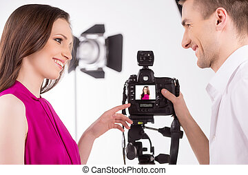 Photographer and model. Young photographer talking to fashion model at studio