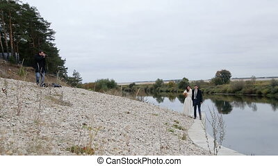 Photographer and newlyweds near the river