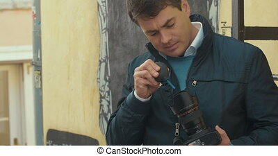 Photographer cleaning camera with lens blower