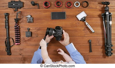 Photographer father with a young son clean the lens before shooting. Wooden table top view. Baby brush touches the lens. Equipment for shooting on the table.
