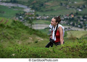 photographer girl climbs a mountain