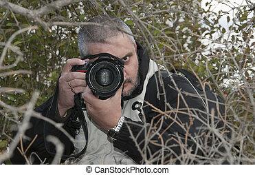 Photographer hidden behind a dense vegetation taking photos.