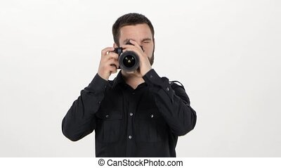 Photographer holds the photography in the studio, man holding the camera and doing photography in the studio, the photographer is standing full face with camera, on white background